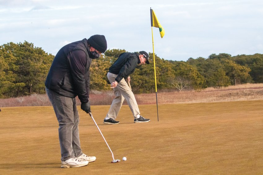 David Macaulay lines up a putt while Jim Wiemann retrieves his ball from the hole during a round of winter golf at the Miacomet Golf Course last week. Off-season play at Miacomet is up significantly over past years.