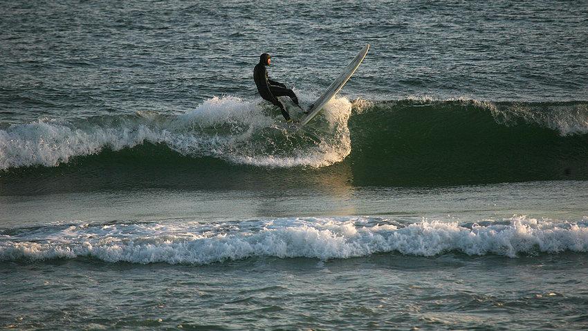 Cameron Marks rides a wave at Cisco Beach on Monday.