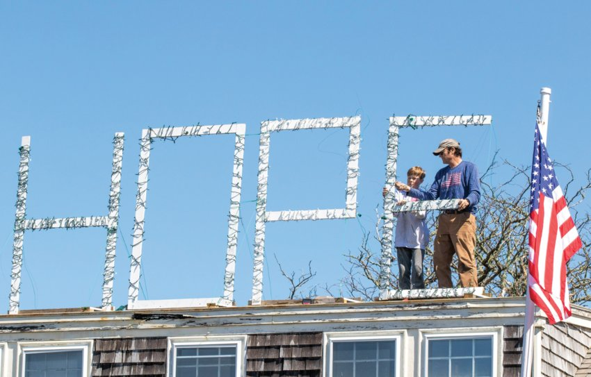 "Chris Fraker with help from his grandson Jackson Agnello stands wooden letters spelling ""HOPE"" wrapped in lights back up on the roof of a Prospect Street home last April following a couple wind storms."