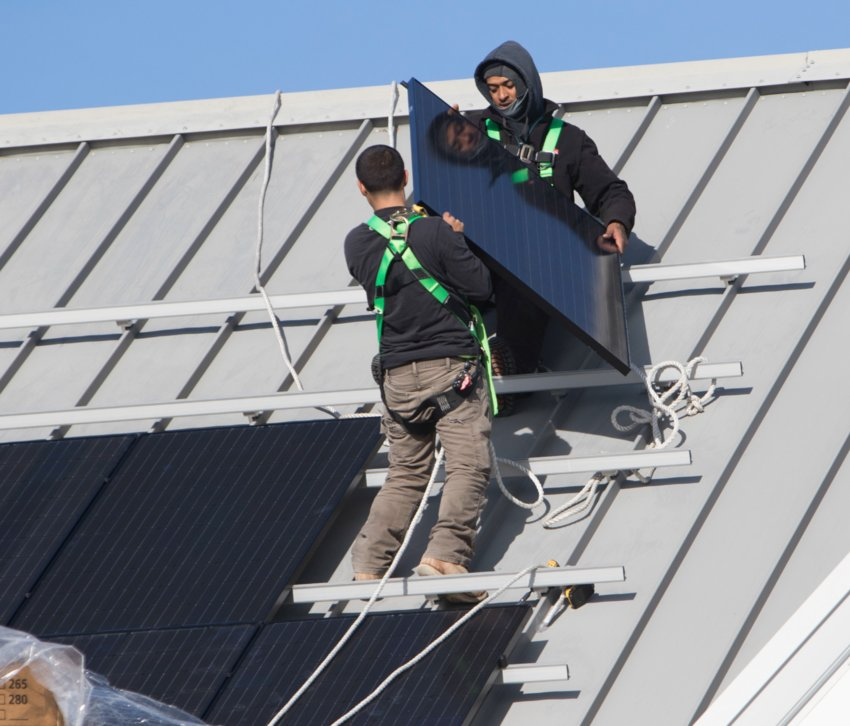 Workmen install solar panels on the roof of the Nantucket Ice rink off Backus Lane.