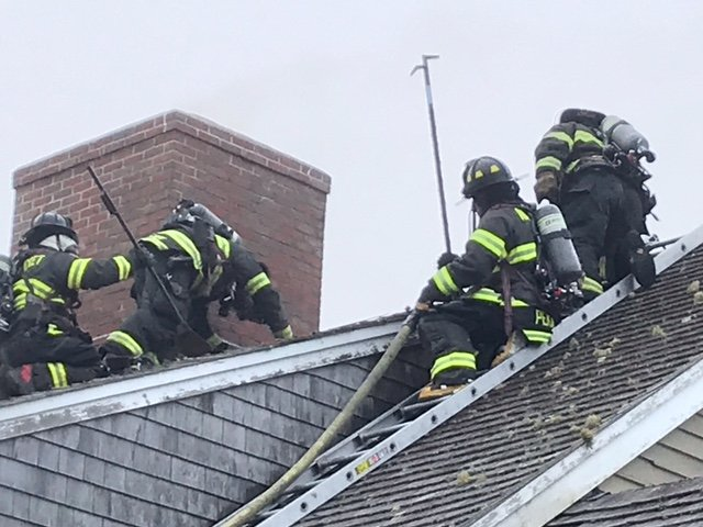 Firefighters on the roof of an Arkansas Avenue home in Madaket Saturday evening.