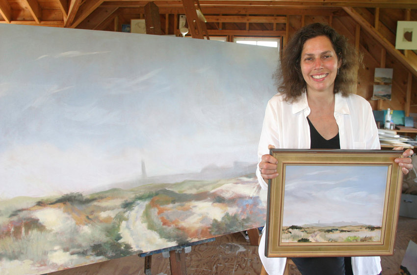 M.J. Dickson holding one version of Great Point at 11 inches by 14 inches and sitting next to a four foot by six foot created by the print in her lap in her studio.