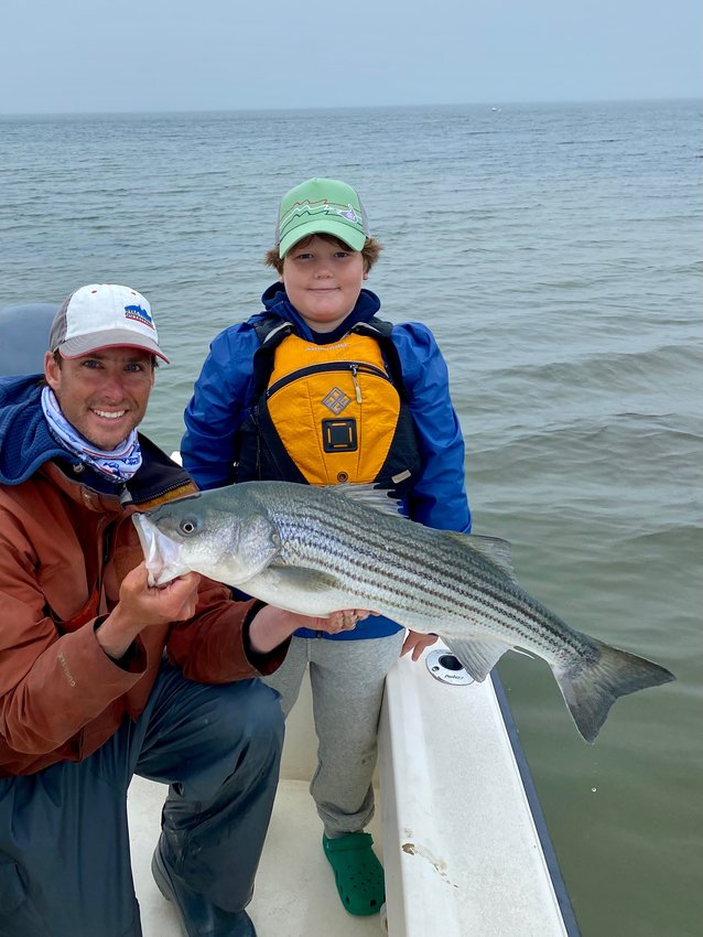 Corey Gammill and Alistair Wood with a striped bass they caught Monday.