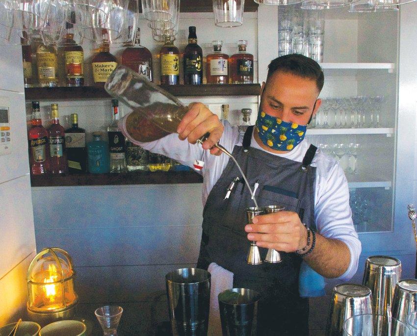 Conrad Meurice pours a cocktail behind the renovated bar at Bar Yoshi.