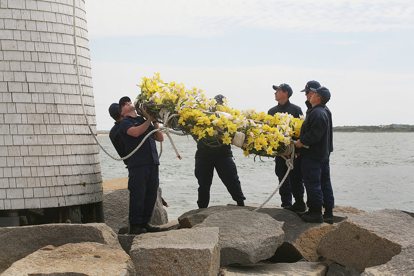 A crew from the US Coast Guard Station Brant Point takes down the daffodil wreath and puts up a flag in honor of Memorial Day and the Fourth of July at the Brant Point lighthouse.