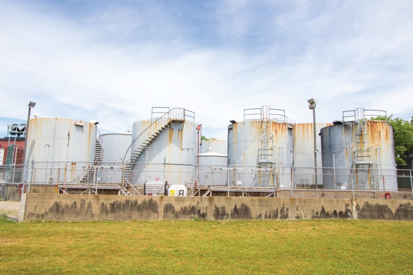 Town officials are seriously considering buying the fuel-tank farm on the downtown waterfront. All but three of the tanks will be removed.