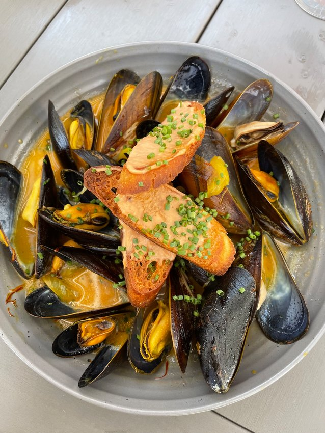 The steamed mussels are served in a light and lemony saffron broth.