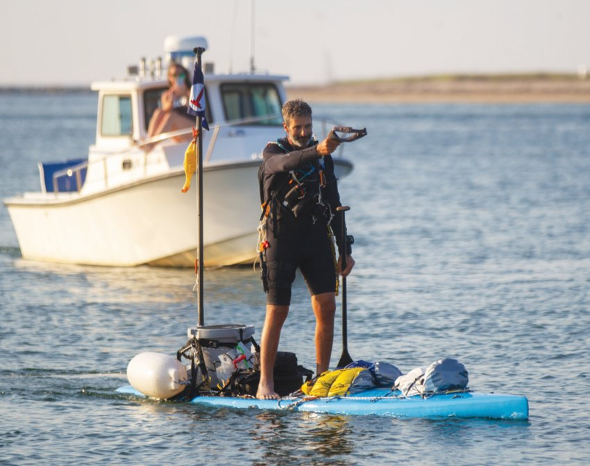 Paddle-boarder Adam Nagler approaches Brant Point Light on Nantucket early Tuesday evening, completing his 450-mile odyssey that began in southern Virginia.