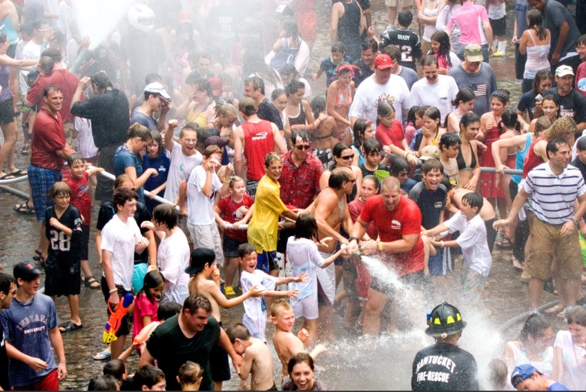 The Fourth of July water fight on Main Street is traditionally mobbed with people dousing each other and the Nantucket Fire Department on the slippery cobblestones.