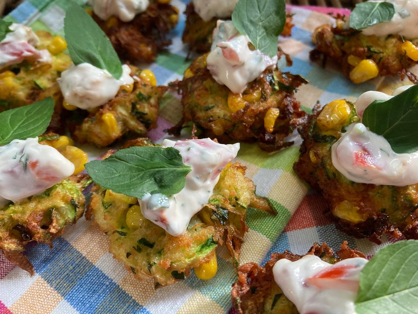 These corn and zucchini fritters are topped off with a dollop of cherry tomato and sour cream dip.