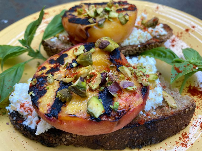 Open-faced grilled peach, ricotta and pistachio toasts.