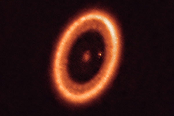 This ALMA image of the PDS 70 system shows the large dust ring that circles the star as well as the dusty glow around the planet PDS 70c, which appears as a bright spot in the large gap.