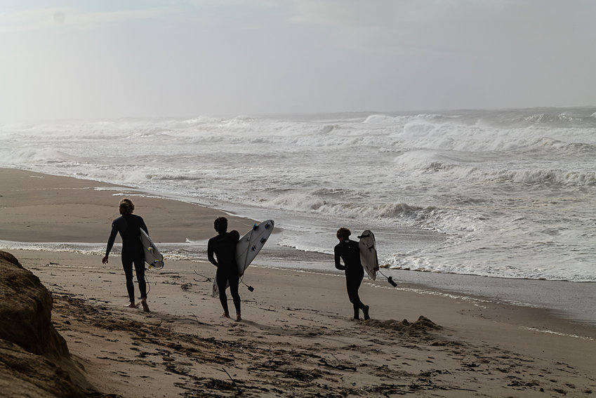 Surfers at the beach in Cisco Sunday.