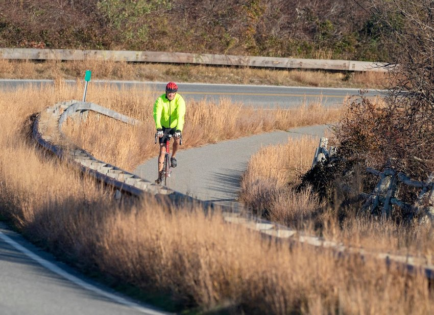 A cyclist rounds the bend on Polpis Road bike path near Sesachacha Pond Monday during a stretch of unseasonably warm weather.