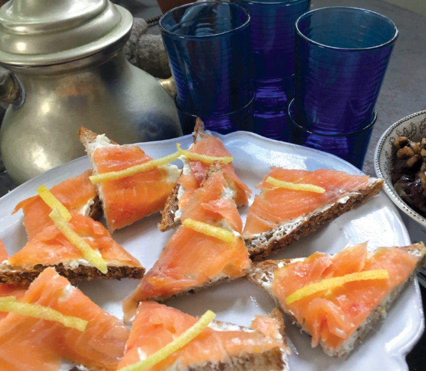 Smoked salmon triangles are made all the more decadent by placing them atop a combination of cream cheese and unsalted butter, and serving with a twist of lemon peel.