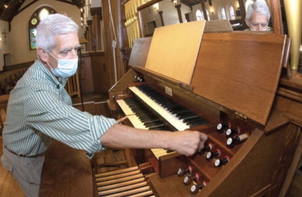 Joe Hammer, director of music at St. Paul's Episcopal Church, works the levers and keys of the church's historic Hutchings-Votey 1902 pipe organ.
