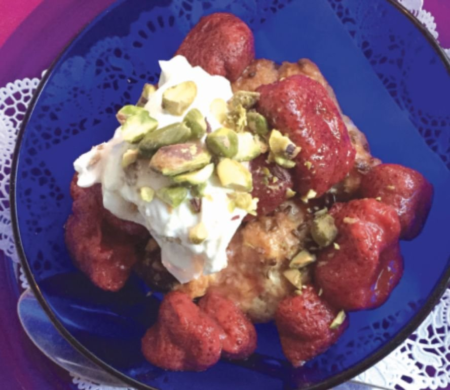 Frozen strawberries poached in cardamom-scented orange juice are delicious when served over a scone with yogurt and pistachios.