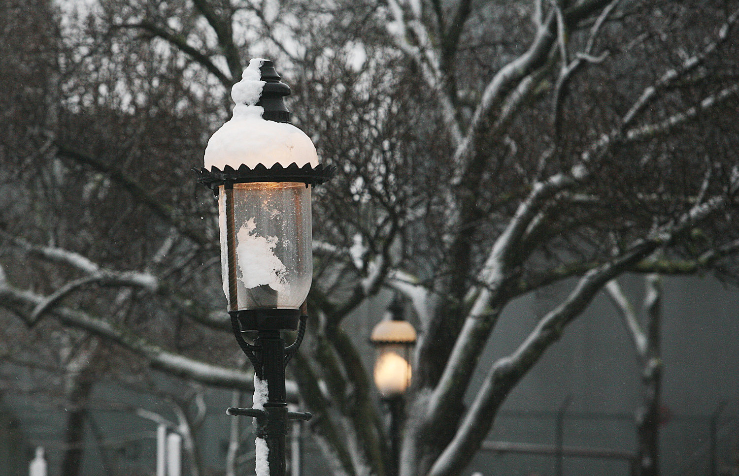 WINTER SCENES -- February 7, 2021 -- Street lamps covered in snow glow on Straight Wharf during Sunday's snow storm. Photo by Ray K. Saunders
