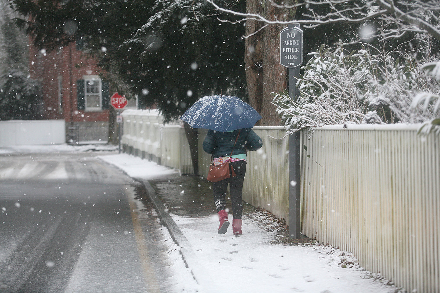 WINTER SCENES -- February 7, 2021 --A woman walks along Pleasant Street during Sunday's snow storm.  Photo by Ray K. Saunders