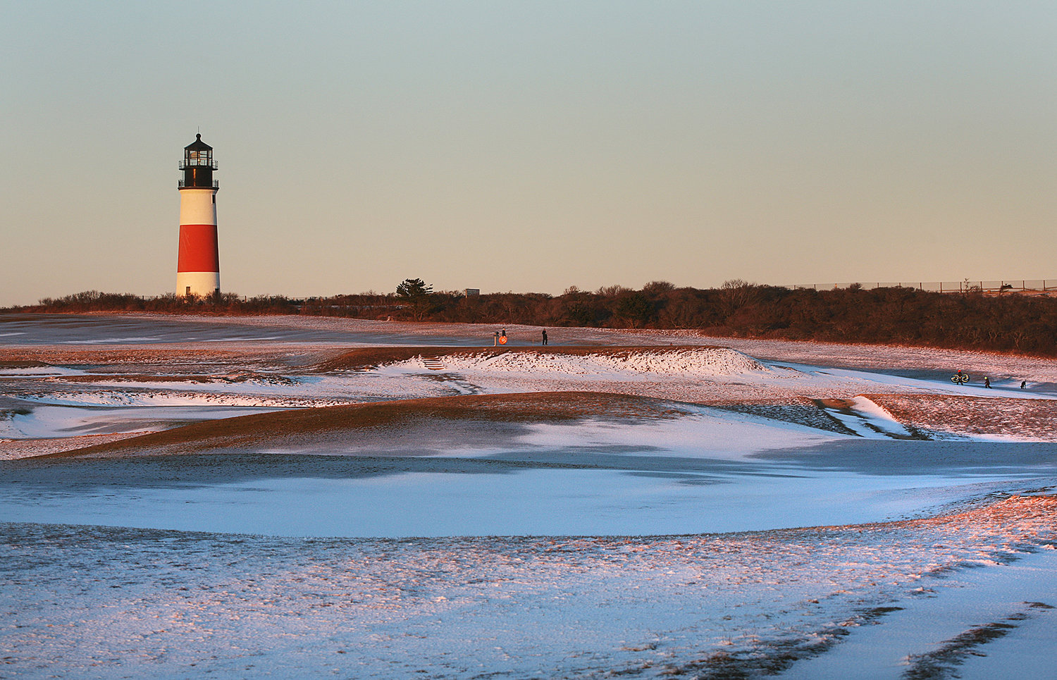 MONDAY, FEBRUARY 8, 2021 -- Snow covers the Sankaty Head Golf Club course as the setting sun illuminates Sankaty Head Lighthouse on Monday following Sunday's snow storm. Photo by Ray K. Saunders