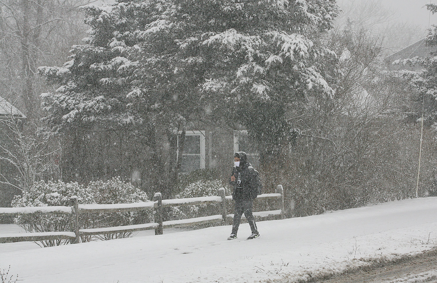 A person, mask on, makes his way through the snow along Surfside Road near the schools.
