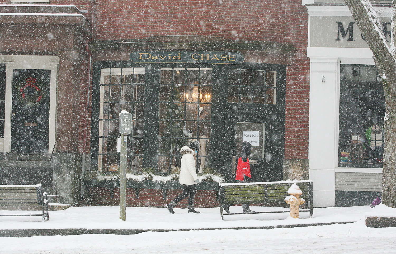 People make their past shops along Main Street during Thursday's snow.