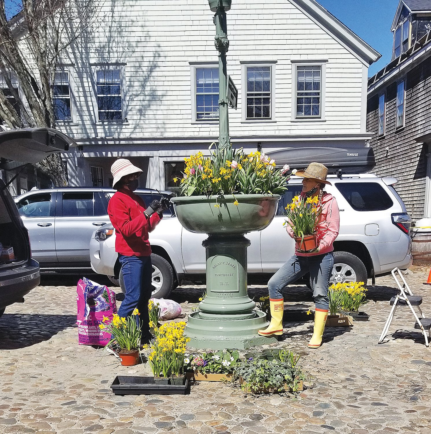 Heidi Drew, left, and Jill Sandole of the Nantucket Garden Club decorate the newly-installed Max Wagner Fountain on Main Street with fresh flowers Saturday.