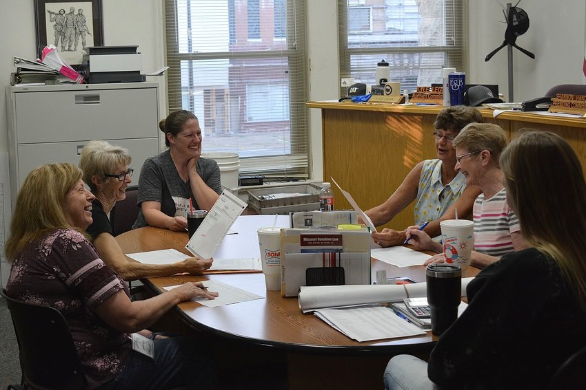From left, Sondra Rogers, LaNelda Presley, Rachel Lightfoot, Bonnie Potts, Janet Timmerman and McKinley Riedesel laugh while waiting in the Polk County Commissioners' Office for the Tuesday, Aug. 3, election ballots to come in.