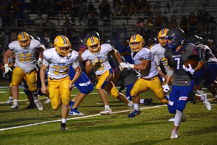 Bolivar's defensive line closes in on Hornet Logan Ahearn, surrounding him on all sides and swatting him to the ground.
