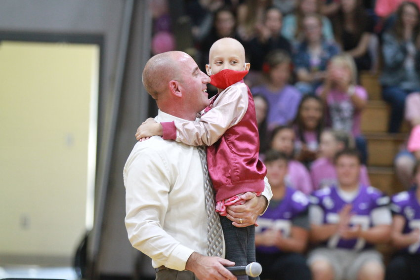 Jason Pursley and Lyndsey Morales hug after she shaved his head at the Skyline assembly on Friday. Pursley is principal of Skyline Elementary School.