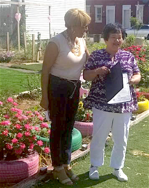 PA State Rep. Carol Hill-Evans, left, recognizes Yoko Enomoto, right, for her dedication to the York community at a surprise presentation in Penn Street Garden.
