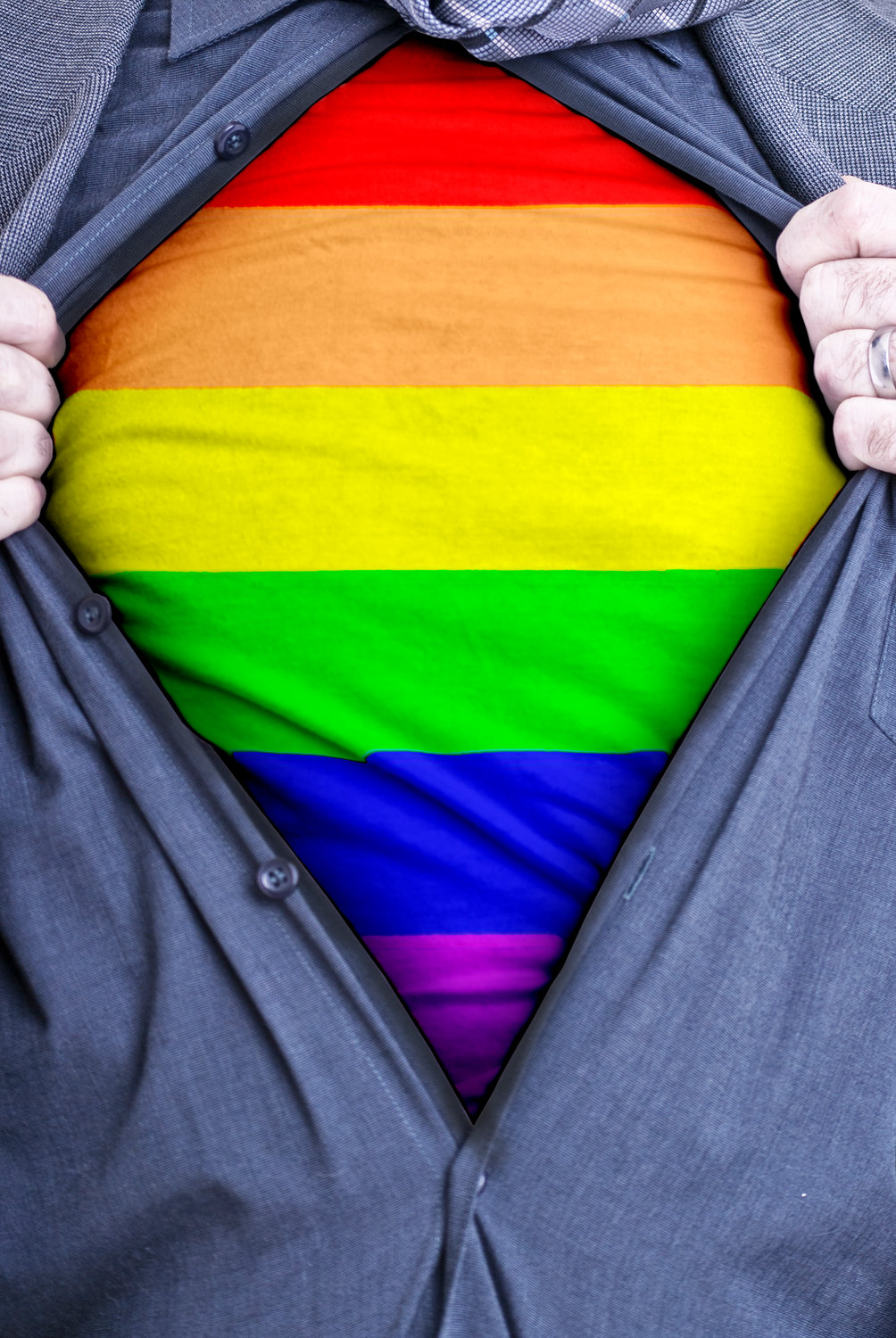 A Gay businessman rips open his shirt and shows how proud he is to be gay by revealing the rainbow flag beneath printed on a t-shirt