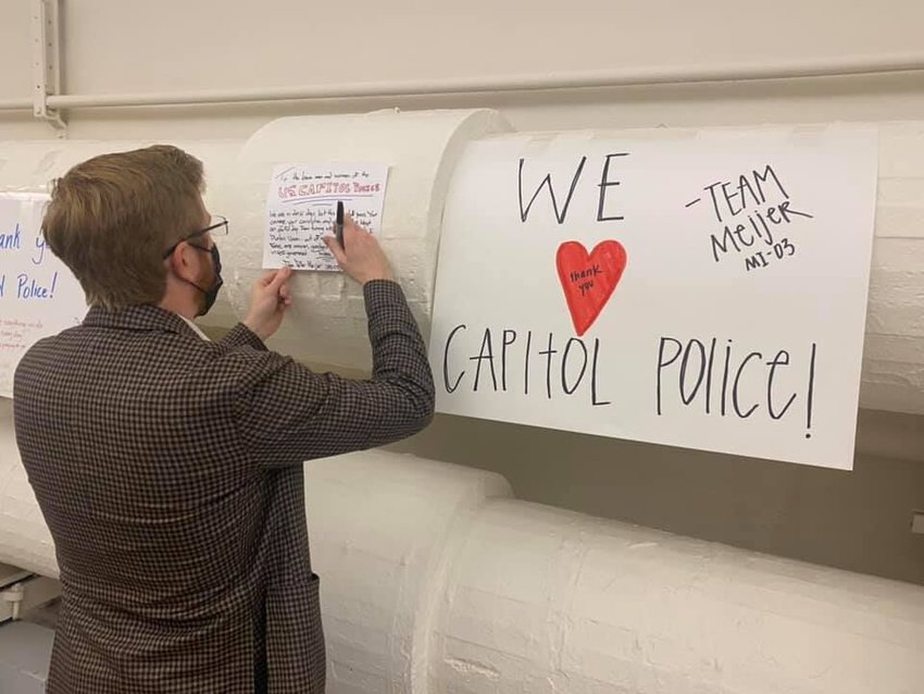 U.S. Rep. Peter Meijer, R-Michigan, signs his name to an appreciative poster for the Capitol Hill Police Department outside his office in Washington, D.C.