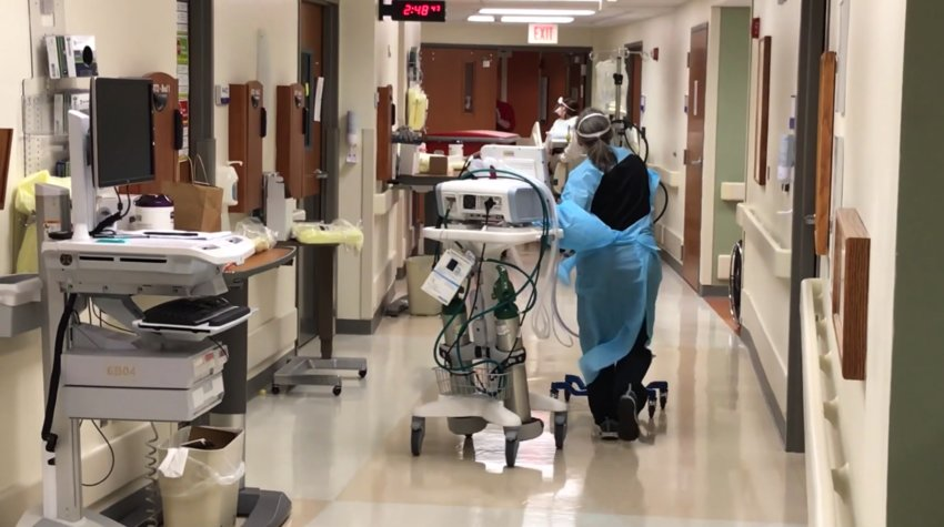 A HEALTH CARE WORKER WEARING A PROTECTIVE GOWN moves respiratory equipment toward a patient room on a COVID unit inside Mercy Hospital in Springfield.