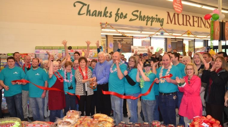 Murfin's Market employees, along with Ozark Chamber and community members, cheer as supermarket founder Chuck Murfin cuts the ribbon in celebration of 35 years.