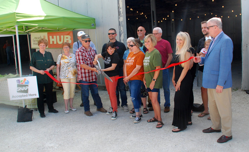 THE OZARK FARMERS MARKET kicked off the 2021 season with a ceremonial ribbon cutting to celebrate joining the Ozark Chamber of Commerce. The Ozark Farmers Market is held every Thursday from 3-7 p.m. at the Workshop at Finley Farms in Ozark. Pictured: Ozark Farmers Market co-founder Katherine Dowdy (holding scissors) surrounded by Ozark Farmers Market board members and Ozark Chamber of Commerce representatives.