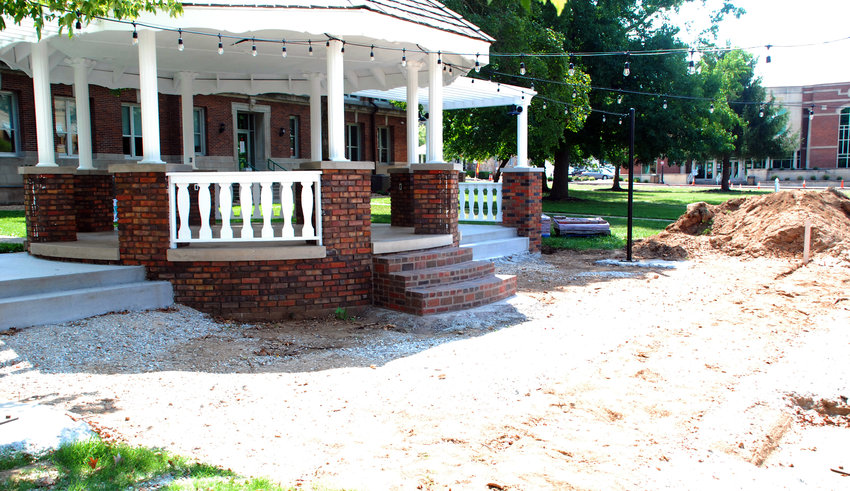 A NEW SIDEWALK is being built alongside the expanded gazebo on the west side of the Ozark square on North Second Street.