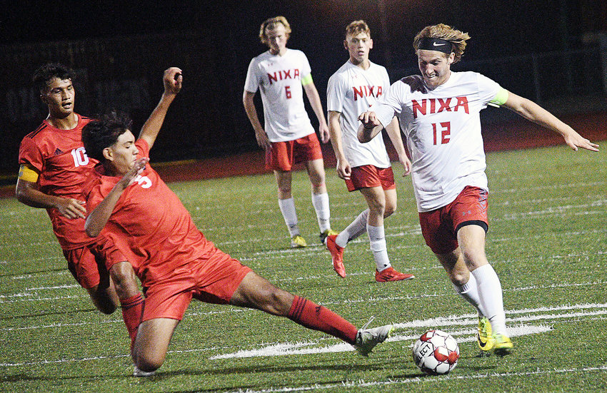 OZARK'S ADRIAN ORTEGA hits the turf to try tip the ball away from Nixa's Landon Myers during the Tigers' 3-2 double-overtime win Tuesday.