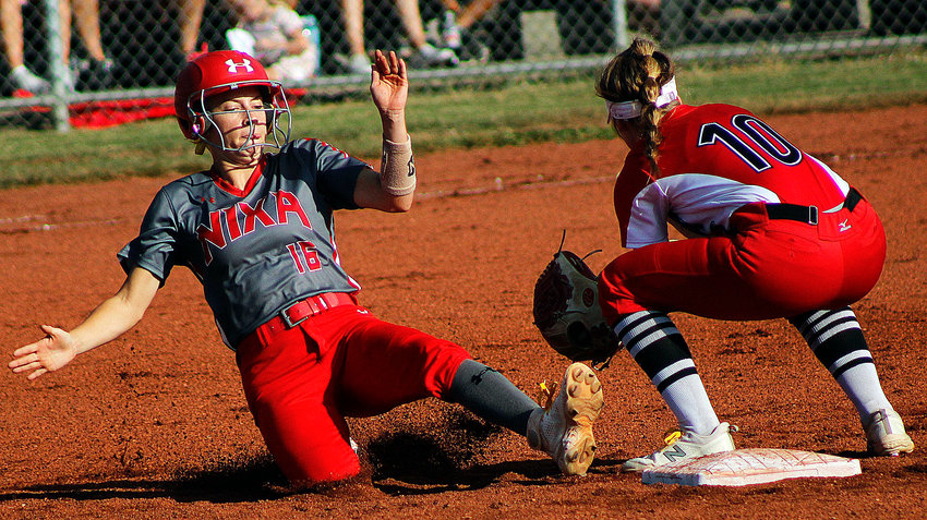 NIXA'S KATIE FAULK steals second base Tuesday, as Ozark shortstop Kaylee Linnebur fields a late throw.
