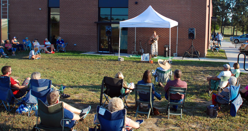 MORE THAN 50 SPARTA RESIDENTS gathered for an outdoor concert by Cindy Woolf of the Creek Rocks at the Sparta branch of the Christian County Library on Sept. 17.