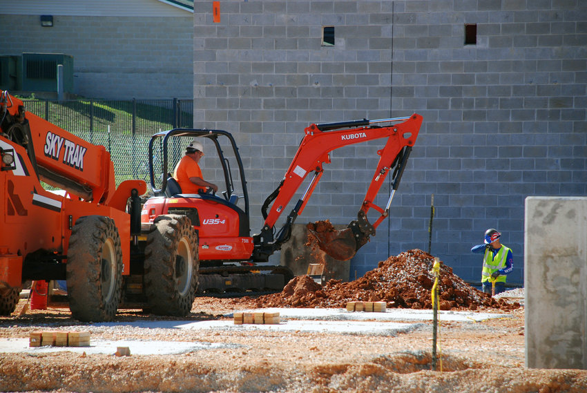 WORKERS USE A TRACKHOE to dig parts of the foundation at the Aetos Center for the Performing Arts on the campus of Nixa High School on Sept. 8, 2021.