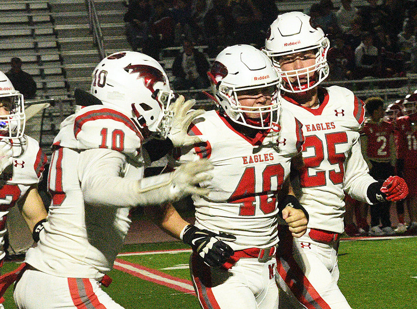 NIXA'S TY HARTMAN receives congrats from Tanner Grant and Cody Breeden following his pick-six in the Eagles' 49-14 win at Carl Junction on Friday.