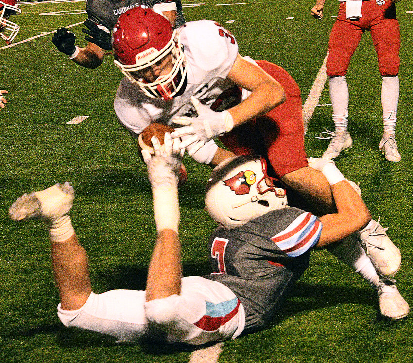 OZARK'S KADIN POWERS holds onto the pigskin while being tackled by a Webb City defender in the teams' matchup Friday.