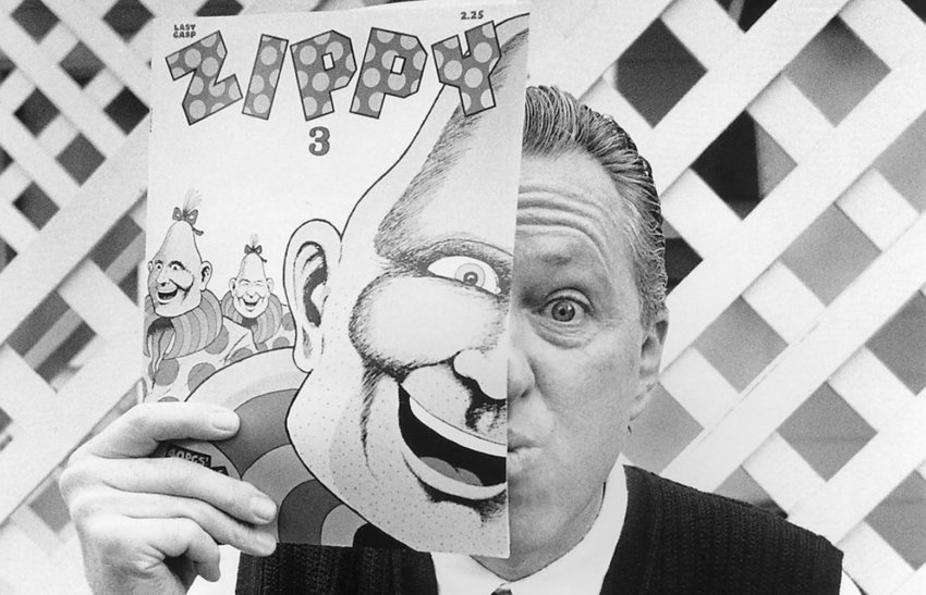 Cartoonist Bill Griffith with an illustration of Zippy the Pinhead.