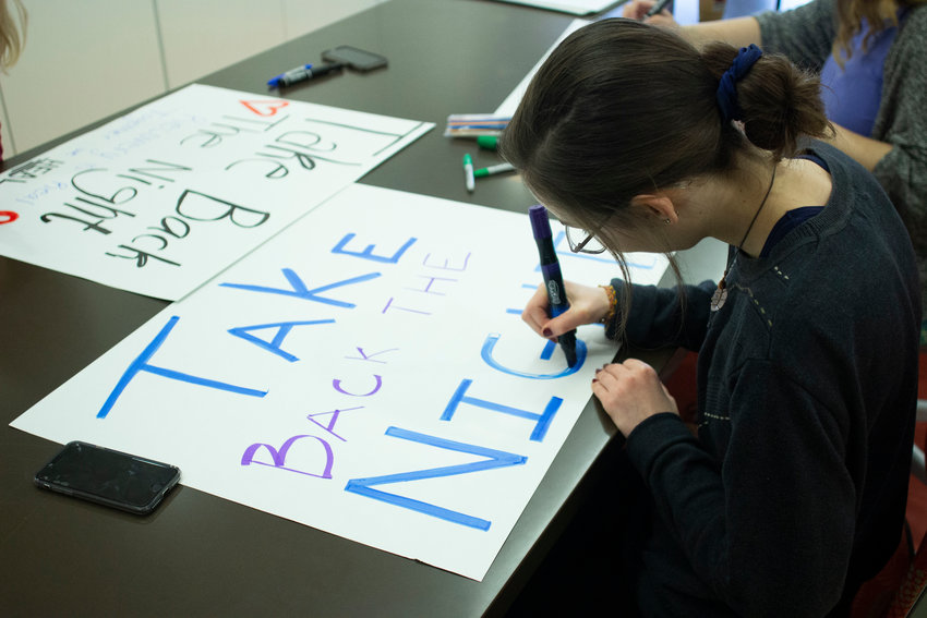 A student works on a sign for Take Back The Night.