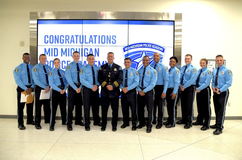 Lansing Police Chief Michael Yankowski poses with 12 of the department's 22 new hires.