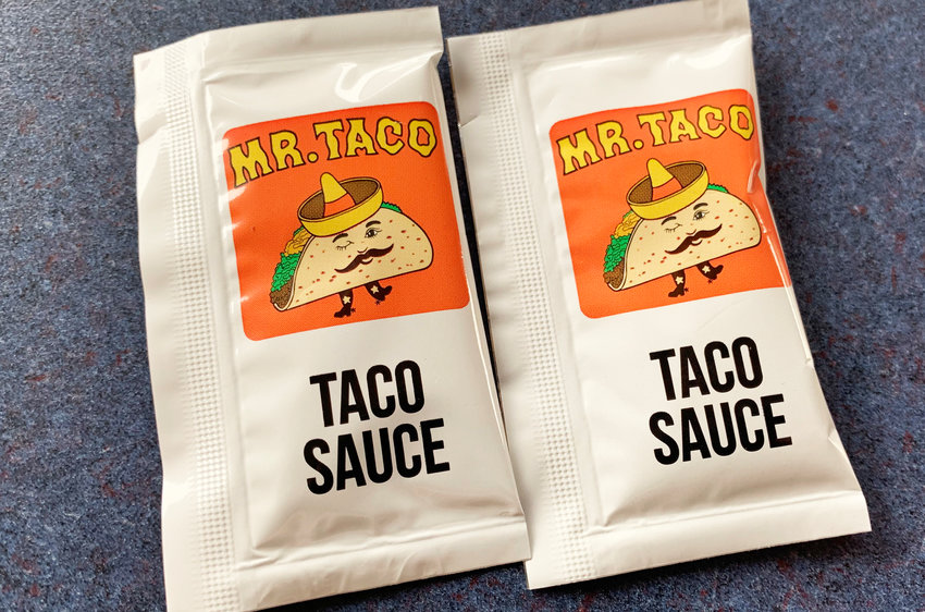 Two packets of Mr. Taco's taco sauce.