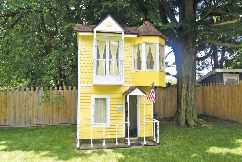 Three types of siding make this an authentic miniature Queen Anne Victorian house.