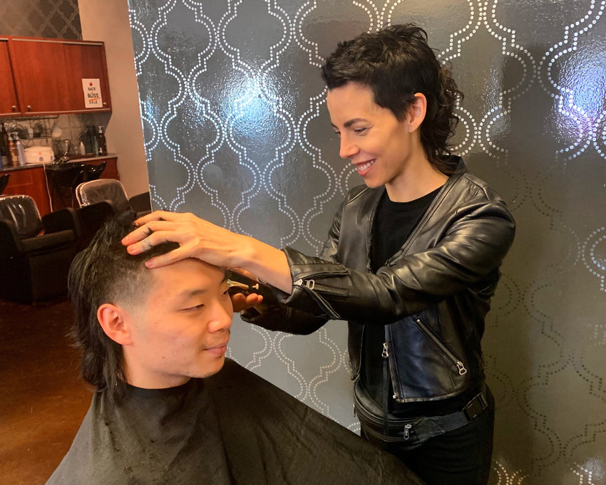 Lansing hairstylist Ashley Medina works on giving client Joshua Lee a mullet.