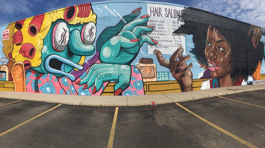 The north wall of the Cadillac parking lot was reimagined by local street artists Samskee and Spiz, as well as national names Birdcap and Sydney James, as part of the Below the Stacks Mural Festival.